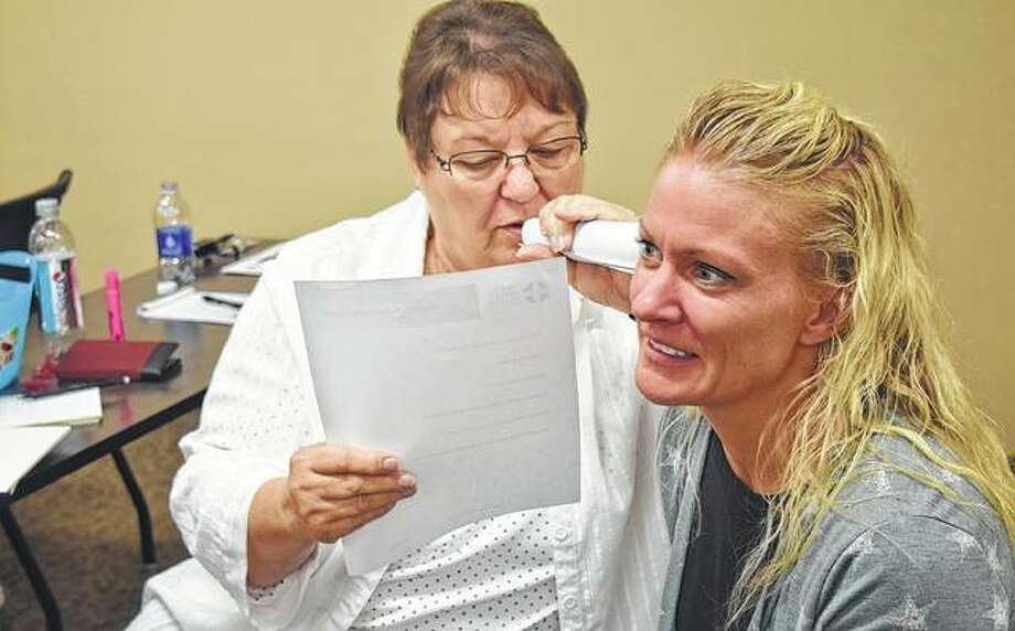 Carol Christensen (right) of Jacksonville tries to have a conversation while Sheila Chapman of Jacksonville whispers in her ear during an exercise Monday that was part of Youth Mental Health First Aid Training. The exercise is supposed to imitate an auditory hallucination. Photo:       Samantha McDaniel-Ogletree | Journal-Courier