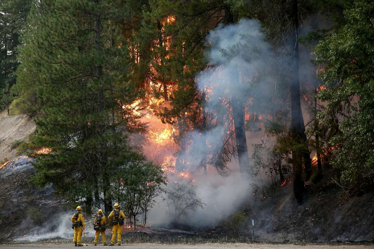 CalFire firefighters monitor flames above State Highway 299 while battling the Carr Fire on July 30, 2018 west of Redding, California. Six people have died in the massive fire, which has burned over 100,000 acres and forced thousands to evacuate since it began on July 23.