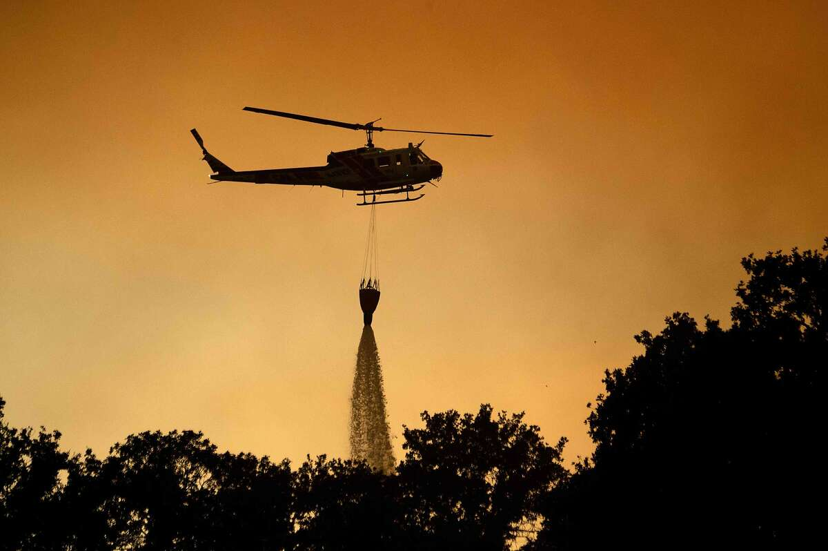 A helicopter drops water while helping to fight the Mendocino Complex fire in Lakeport, California, on July 30, 2018. The Mendocino Complex -- made up of two fires -- has burned more than 24,000 acres in total since July 27. Thousands of firefighters in California made some progress against several large-scale blazes that have turned close to 200,000 acres (80,940 hectares) into an ashen wasteland, destroyed expensive homes, and killed eight fire personnel and civilians in the most populous US state. / AFP PHOTO / JOSH EDELSONJOSH EDELSON/AFP/Getty Images