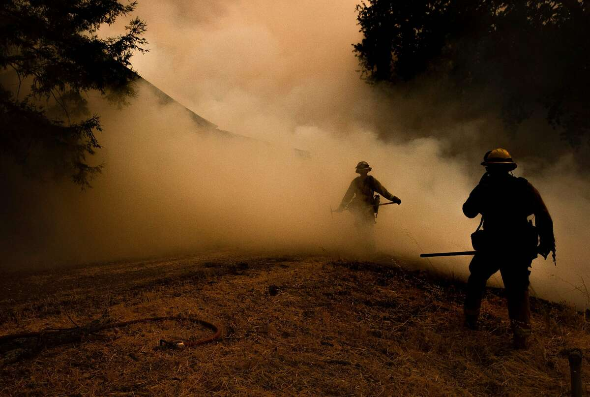 A firefighter walks through smoke from the Mendocino Complex fire in Lakeport on July 30, 2018.