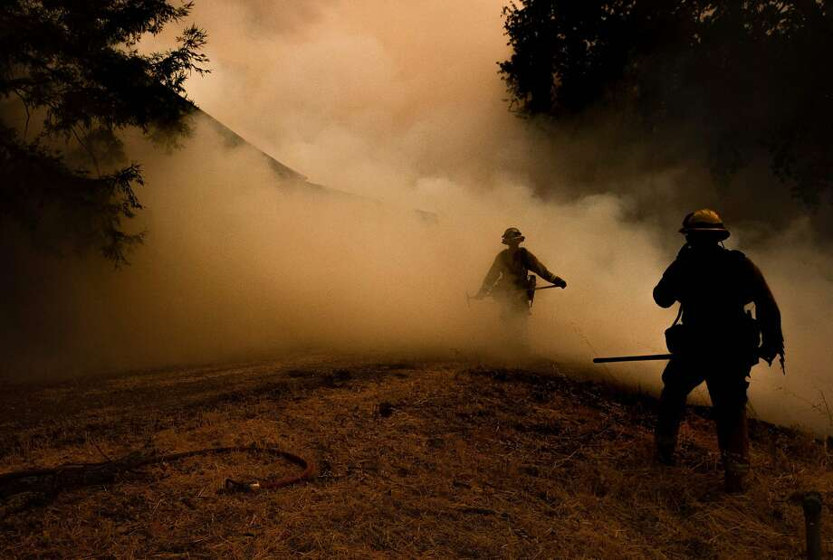 A firefighter walks through smoke as flames approach a home in the River Fire outside Lakeport (Lake County). Photo: Josh Edelson / AFP / Getty Images