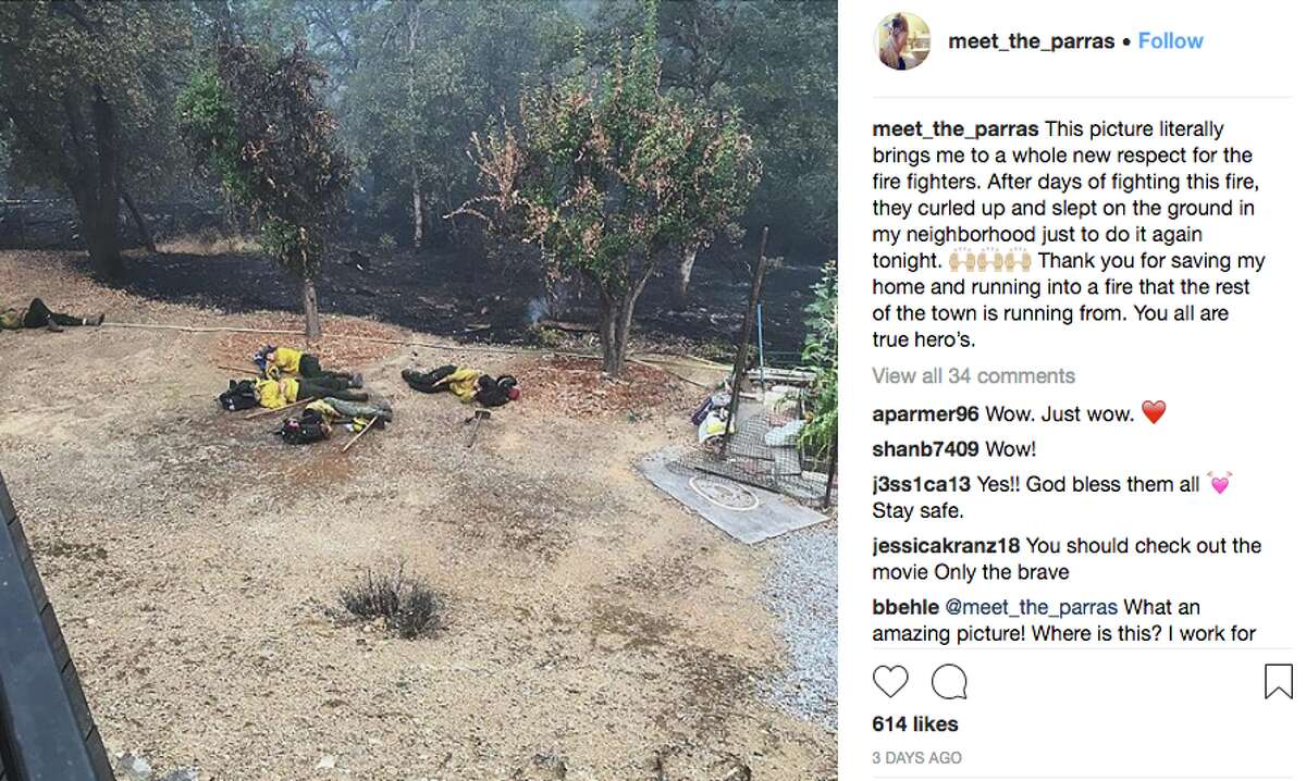 Firefighters sleep during a lull in a Redding neighborhood while fighting the Carr Fire.
