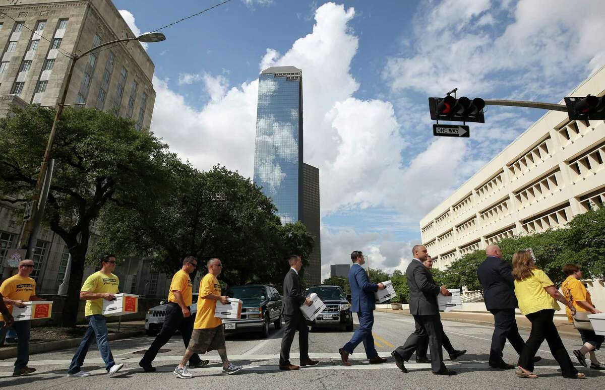 Houston firefighters carry boxes filled with more than 32,000 signatures to put equal pay on the ballot as they walk across Bagby Street to the City Hall Annex building Monday, July 17, 2017, in Houston. ( Godofredo A. Vasquez / Houston Chronicle )