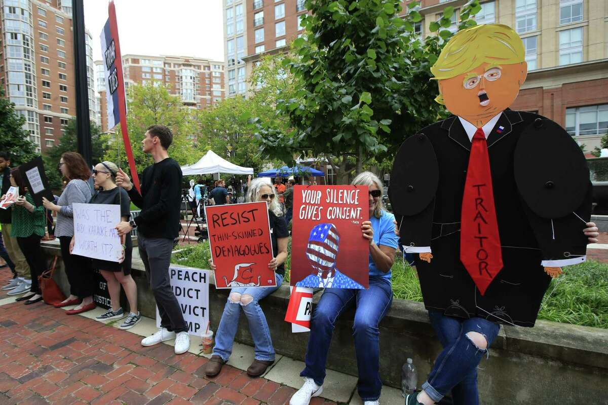Protesters hold their banners in front of the Alexandria Federal Court in Alexandria, Va., Tuesday, July 31, 2018, on day one of Paul Manafort's trial. (AP Photo/Manuel Balce Ceneta)