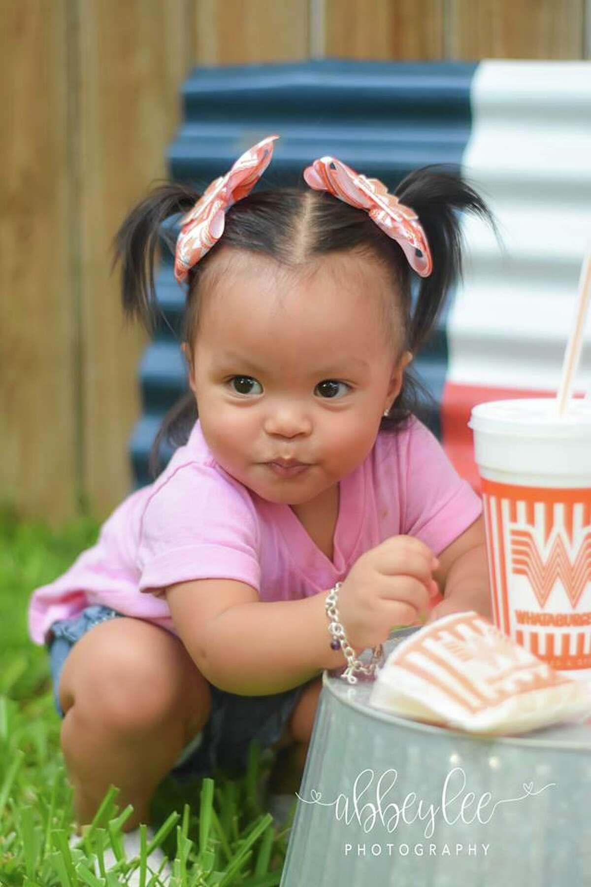 Adelyn Gonzales' love for the two Texas institutions were on full display in a series of H-E-B- and Whataburger-themed photos taken by her aunt, Abbey Lopez, of AbbeyLee Photography. Though the infancy of Adelyn's infatuation coincided with her infancy, her allegiance to the two brands is full grown.