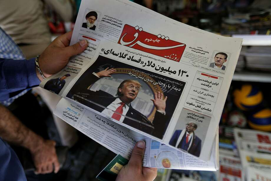 A man glances at a Tehran newspaper headline over Iran's sinking currency as U.S. sanctions loom. Photo: Atta Kenare / AFP / Getty Images