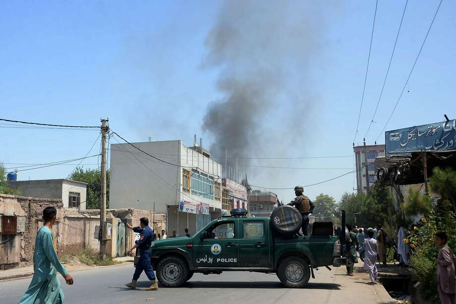 Afghan security personnel secure a road as smoke billows from the site of suicide attack as an ongoing attack between Afghan security force and suicide attackers in Jalalabad. Photo: Noorullah Shirzada / AFP / Getty Images