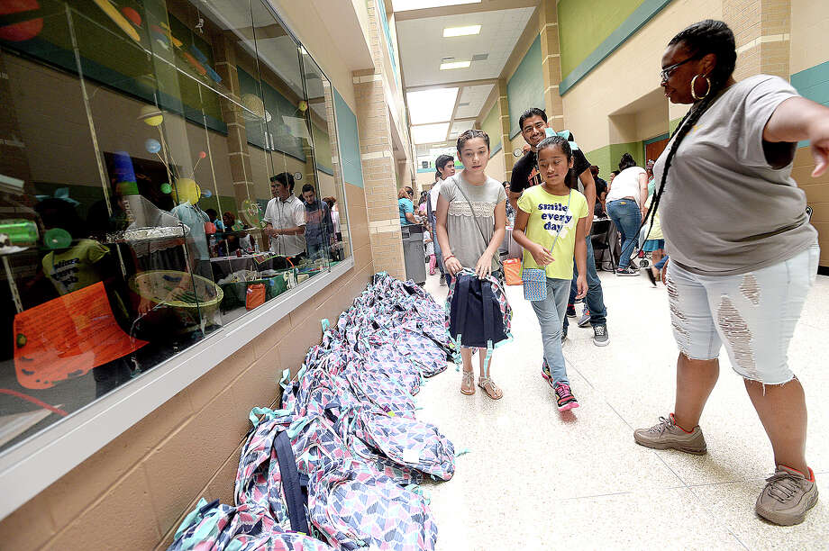Children select from an assortment of styles as they pick up their backpacks during the Back to School event at South Park Middle School. Legacy Community Health sponsored the annual event, giving out backpacks and other supplies. Saturday's event included give aways and information from several other community organizations, registration for school and activities and games for children. Saturday, July 28, 2018 Kim Brent/The Enterprise Photo: Kim Brent/The Enterprise