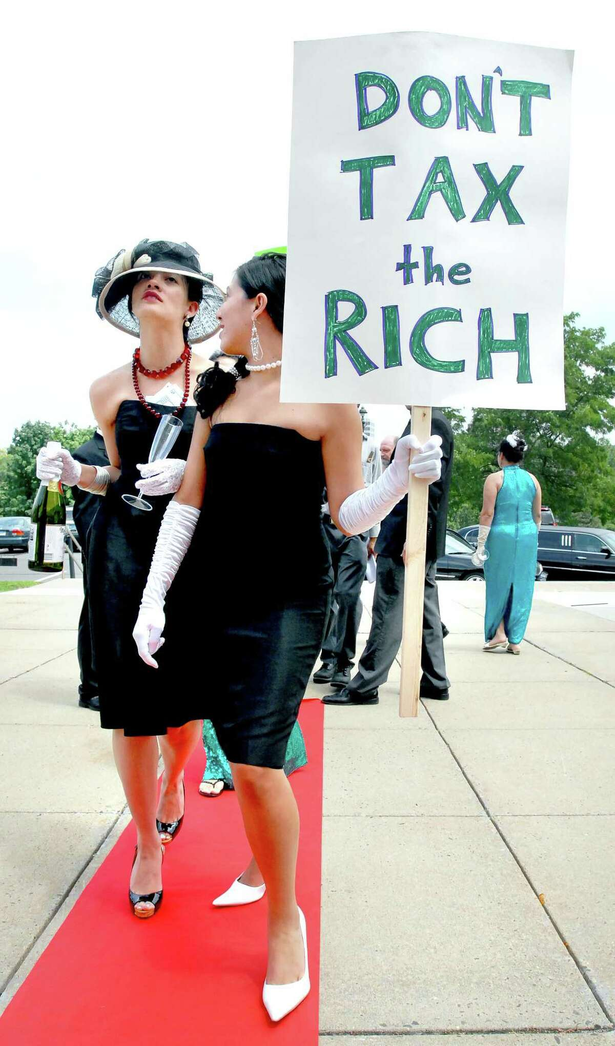 hart-billionaires-ag-7/30/09 Marisa Lindsey (left) and Nicole Diaz (right) of Billionaires for Budget Cuts walk the red carpet to a press conference on the steps of the Capitol Building in Hartford on 7/30/09 making light of Governor M. Jodi Rell's Executive Order cutting funding for public services without increasing taxes for the wealthy. Both are from Hartford. Photo by Arnold Gold AG0320A
