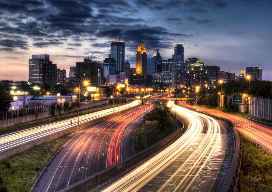 Downtown Minneapolis skyscrapers and skyline and light trails on road  with slightly cloudy at sunset in Minneapolis, US. Photo: Greg Benz/Getty Images