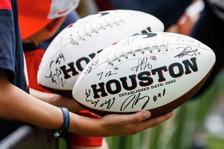 A fan holds autographed Houston Texans footballs during training camp at the Greenbrier Sports Performance Center on Tuesday, July 31, 2018, in White Sulphur Springs, W.Va.