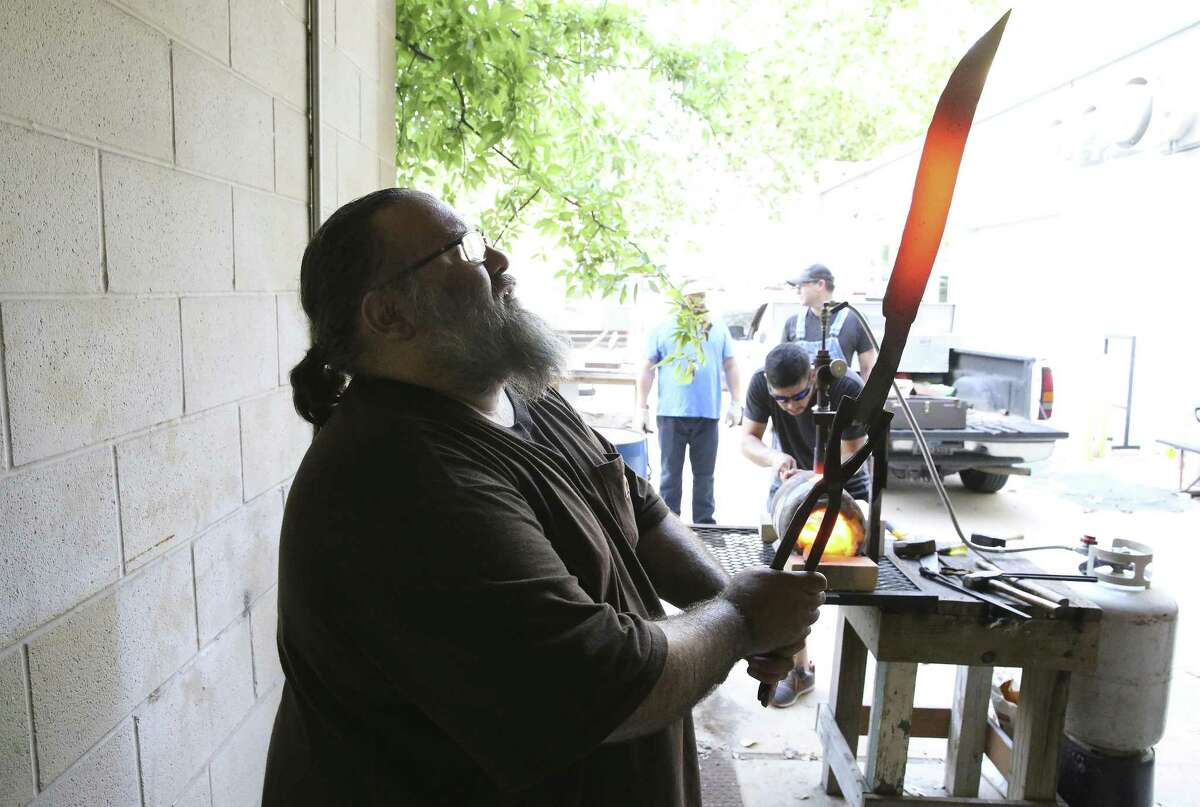 Tobin Nieto examines the form of a large blade as he teaches a class in bladesmithing at the Southwest School of Art. The age-old art seems to be enjoying something of a renaissance, especially in Texas