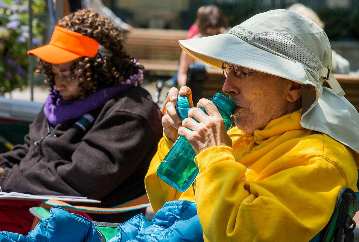 Faster Beth Oglvie of Castro Valley, right, sips water during the second day of a three-day hunger strike in front of the Oakland Federal Building in Oakland, Calif. Tuesday, July 31, 2018 hosted by Bay Area mothers protesting the separation of families at the border.