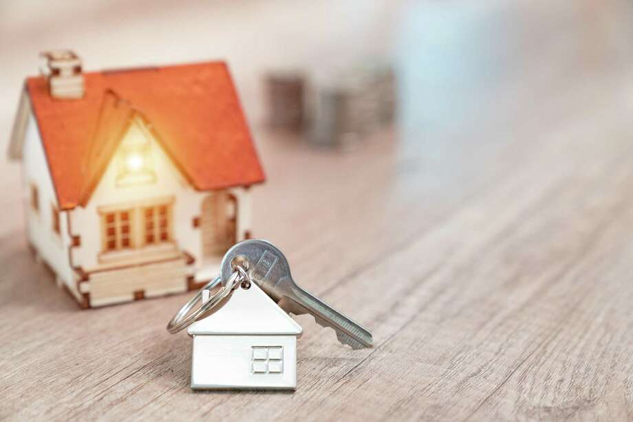 House key on a house shaped keychain resting on wooden floorboards concept for real estate, moving home or renting property Photo: Witthaya Prasongsin /Getty Images / lOvE lOvE