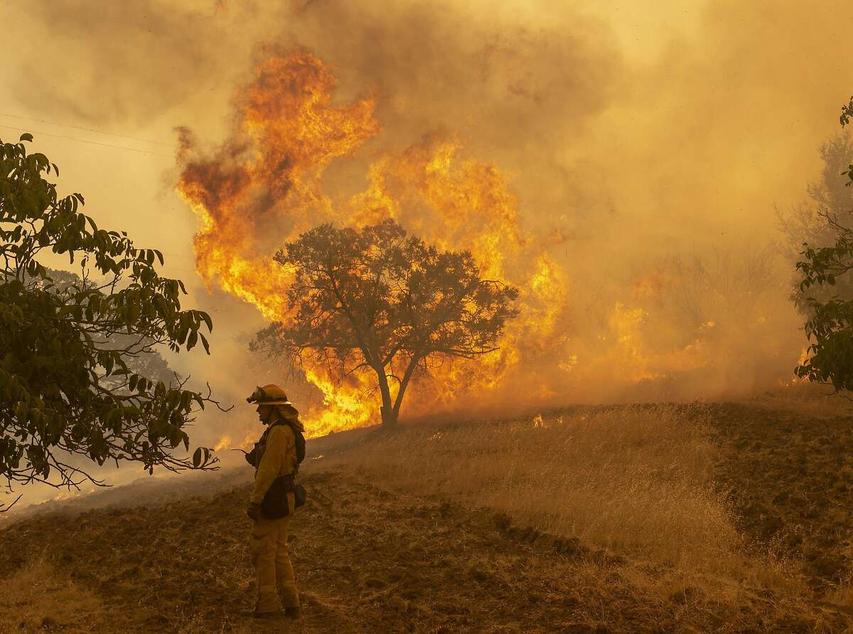 Firefighter Wyatt Belden from Gold Ridge Fire Protection in Sonoma County, monitors a fire burning off Keck Road, just west of Lakeport, Calif., on Monday, July 30, 2018. (Jose Luis Villegas/The Sacramento Bee via AP)