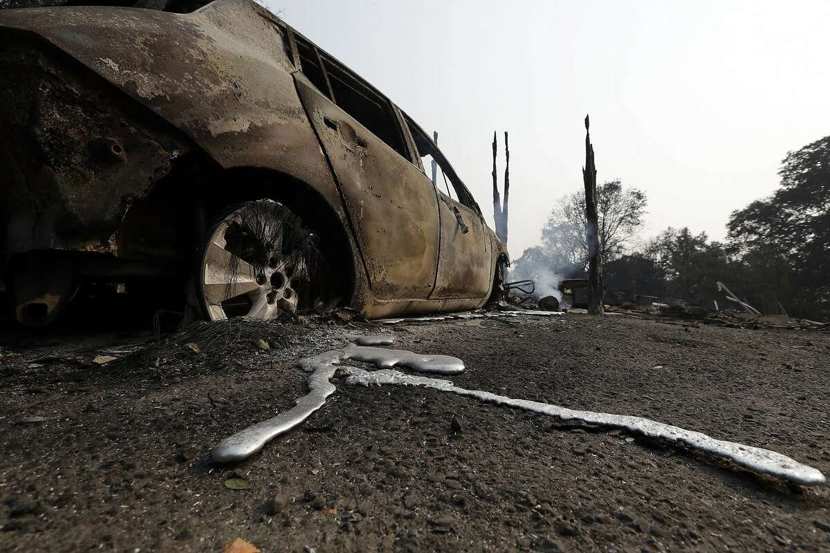 Melted metal is seen under a wildfire- damaged car Tuesday, July 31, 2018, in Lakeport, Calif. Battalion Chief John Messina said Tuesday fire crews slowed the spread of one of the blazes into towns near Clear Lake, including Lakeport, a city of 5,000. He says the fire instead spread into the Mendocino National Forest. (AP Photo/Marcio Jose Sanchez)