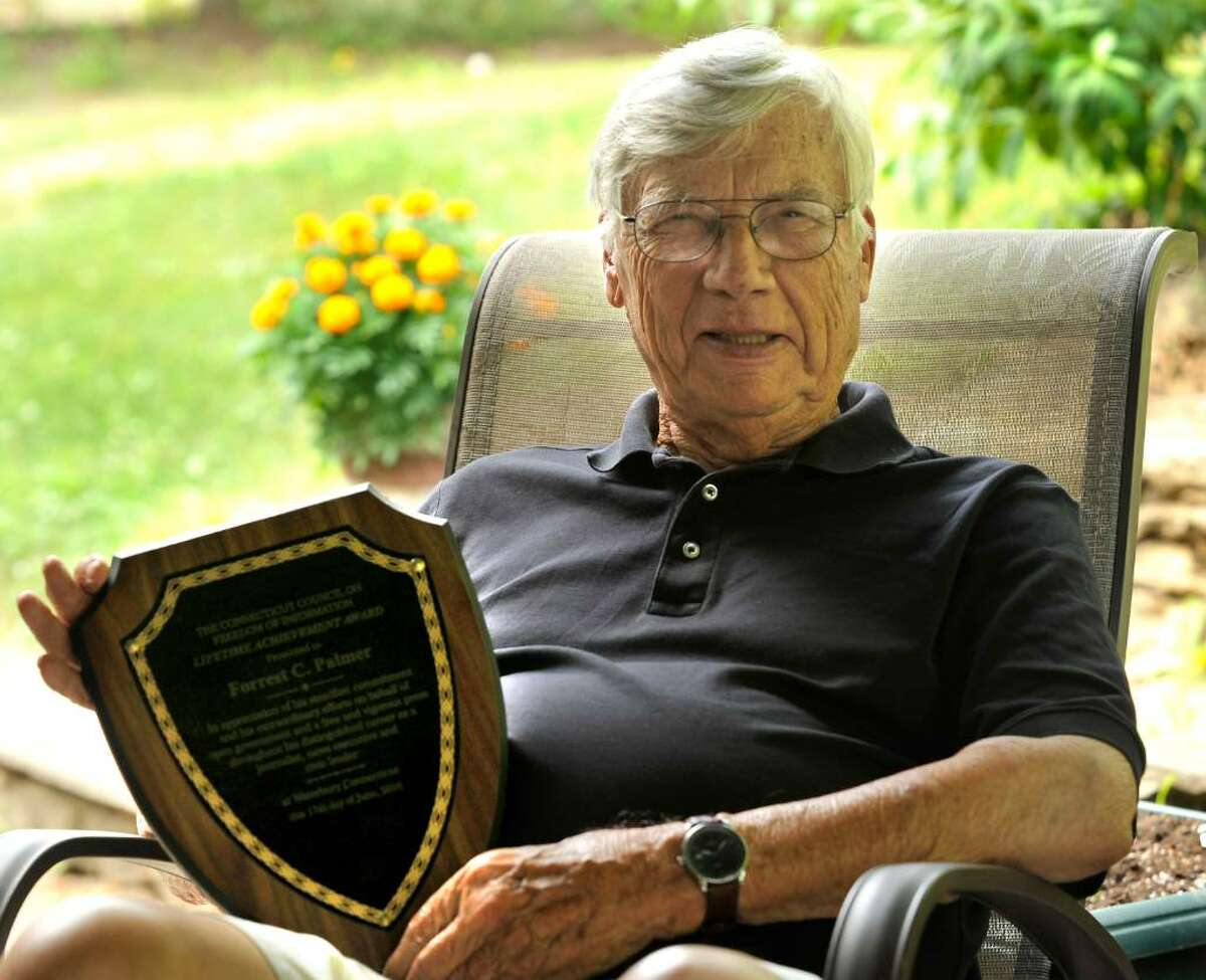 Forrest Palmer holds the lifetime achievement award he recently received from the Connecticut Council on Freedom of Information. He is seated on the patio of his Southbury home,Thursday, July 8, 2010.