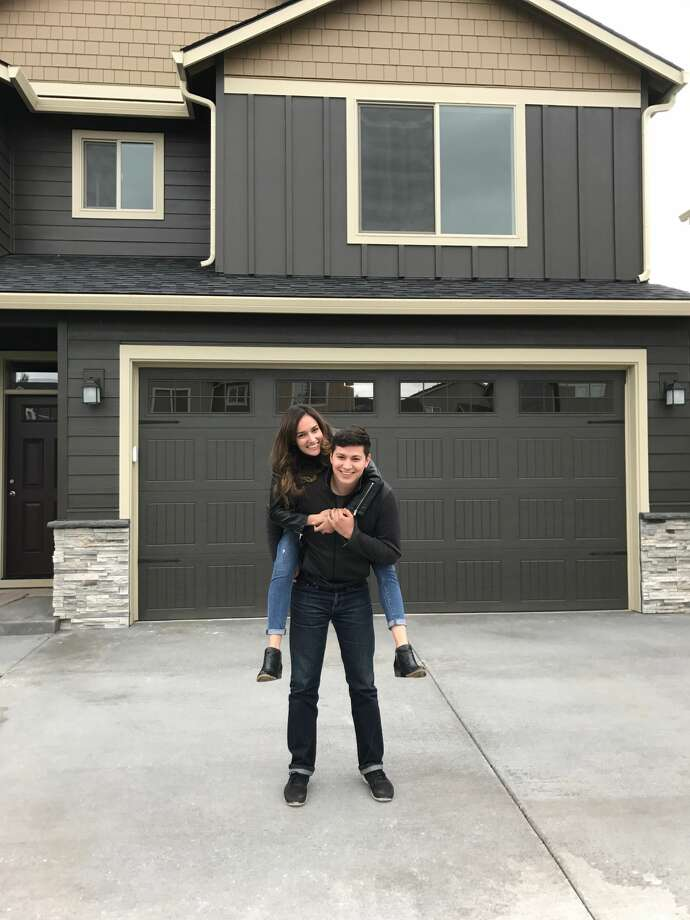 Nancy Fimbrez, 25, stands with her husband Stephen in front of the home they purchased in Vancouver, Wash., on the day they closed.