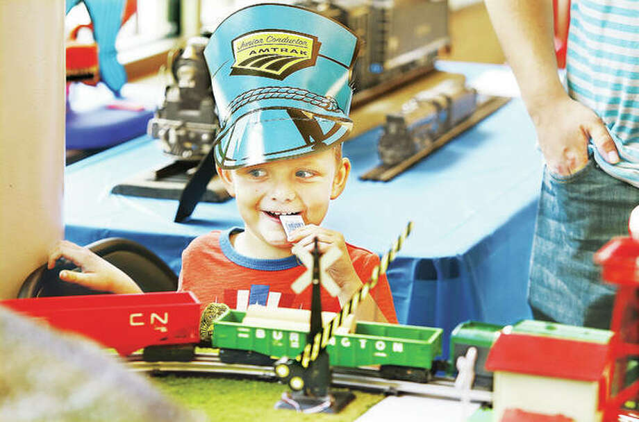 Andrew Ellison, 5, of East Alton, wearing his junior Amtrak conductor hat and getting ready to blow his train whistle, watches a model railroad train pass by on a display at the 4th annual Train Day at the Alton Regional Multimodal Transportation Center in Alton. Hundreds of people, many children, attended the event Tuesday, as the first year Train Day has been held at the new Amtrak station as a part of this year's Kid'Cation event. Photo:     John Badman | The Telegraph