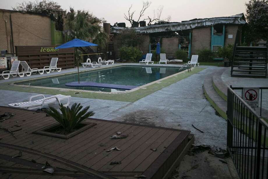 A view of the swimming pool is shown with the charred remains of Building 500 standing behind it at Iconic Village Apartments in San Marcos. Five people were found dead and a sixth person suffered severe injuries in a large fire that swept through the property during the early morning hours of July 20. Photo: Josie Norris /San Antonio Express-News / © San Antonio Express-News