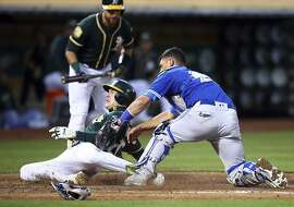 Oakland Athletics' Mark Canha steals home plate as Toronto Blue Jays catcher Luke Maile , right, makes the tag in the third inning of a baseball game Tuesday, July 31, 2018, in Oakland, Calif. (AP Photo/Ben Margot)