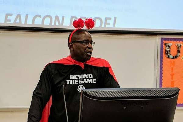 Darryl Hemphill wears a cape and other gear to illustrate the role coaches play as heroes during his presentation Tuesday.