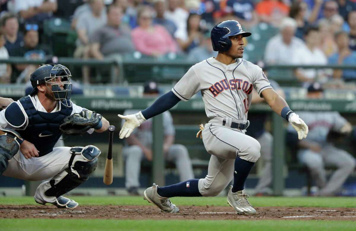 Houston Astros' Tony Kemp, right, singles as Seattle Mariners catcher Chris Herrmann looks on in a baseball game Tuesday, July 31, 2018, in Seattle. (AP Photo/Elaine Thompson)