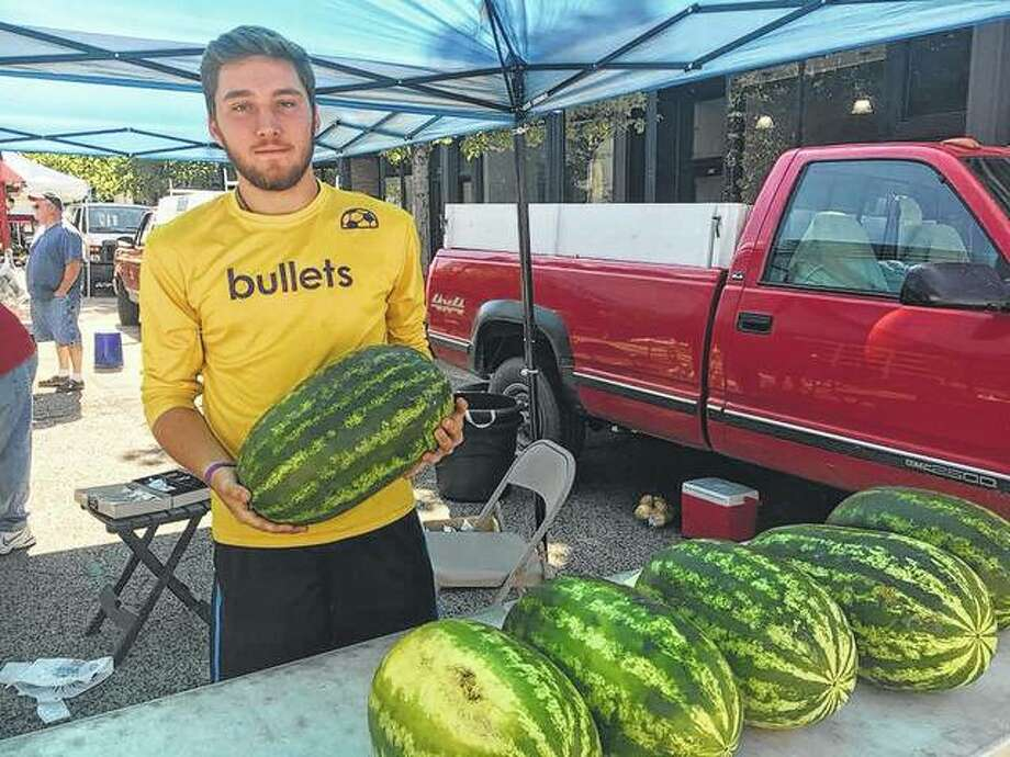 A vendor at the Old Capitol Farmers Market in downtown Springfield shows off a fresh, in-season watermelon. Photo:       Photo Provided