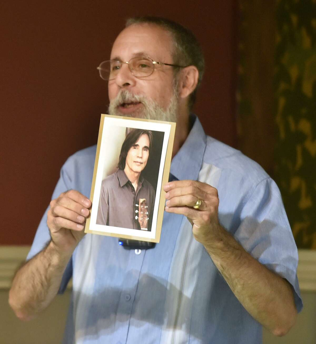 New Haven, Connecticut - Tuesday, July 31, 2018: Stan Heller, Administrator of Promoting Enduring Peace, shows a photo of singer/songwriter Jackson Browne who is this year's recipient of its annual Gandhi Peace Award during a press conference Tuesday at the New Haven Free Public Library in New Haven.
