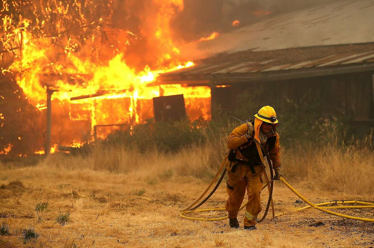 A West Covina firefighter pulls hose away from a horse barn that burns as the River Fire moves through the area on July 31, 2018 in Lakeport, California. The River Fire has burned over 27,000 acres, destroyed 7 homes and stands at 8 percent contained.