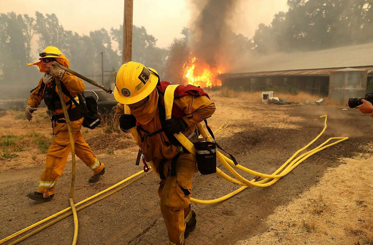 West Covina firefighters pulls hose away from a horse barn that burns as the River Fire moves through the area on July 31, 2018 in Lakeport, California. The River Fire has burned over 27,000 acres, destroyed seven homes and stands at only eight percent contained.