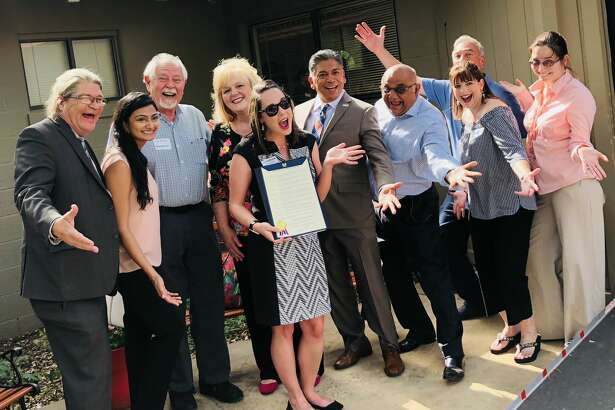 Mayor Jerry Morales is surrounded by guests. --- VisitMidland hosted its quarterly Four to Sixer Mixer May 8 at the George W. Bush Childhood Home. At the event, Mayor Jerry Morales read a proclamation kicking off National Tourism Week. About 100 people attended and toured the home.