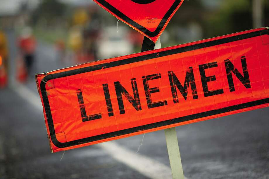 """Zoe Carew said it wasn't right when she saw crews working on power lines near a """"LINEMEN"""" sign. Photo: / Associated Press"""