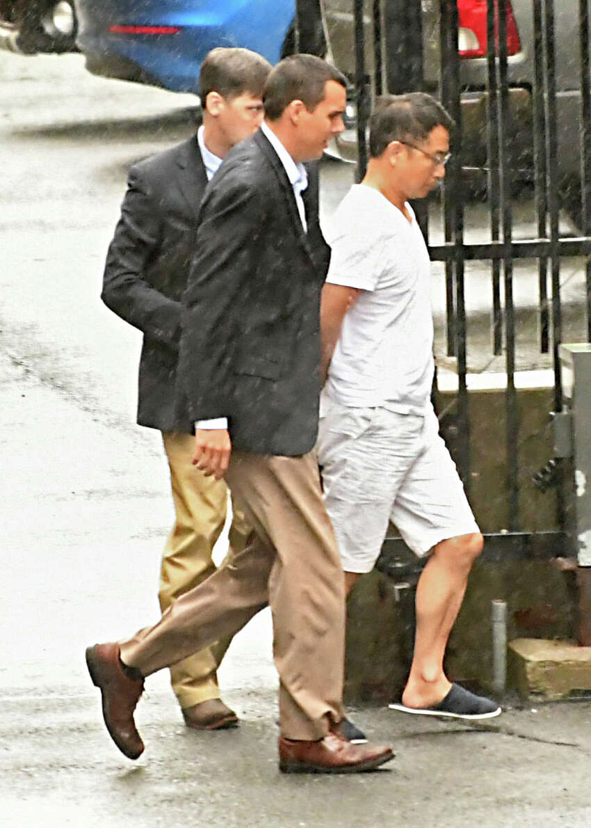 FBI agents escortGeneral Electric engineerXiaoqing Zheng to his arraignment at U.S. District Court in Albany on charges of theft of trade secrets.(Lori Van Buren/Times Union)
