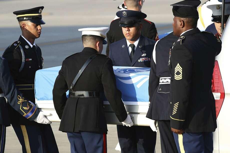 Honor guards carry the remains of U.S. servicemen killed in the Korean War at a South Korean air base. Photo: Chung Sung-Jun / Associated Press