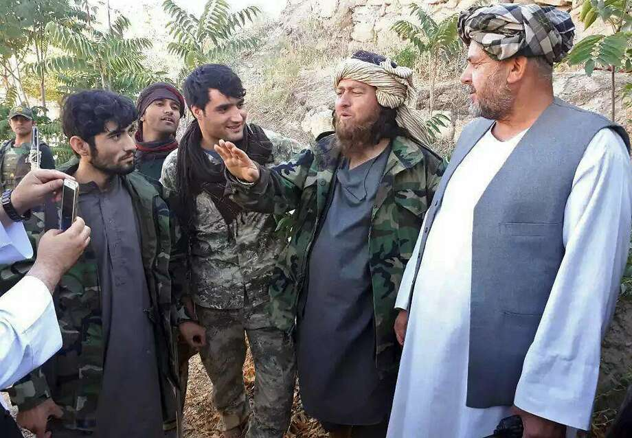 Islamic State fighter (second right) speaks to a journalist after surrendering in Jawzjan province. Photo: Associated Press