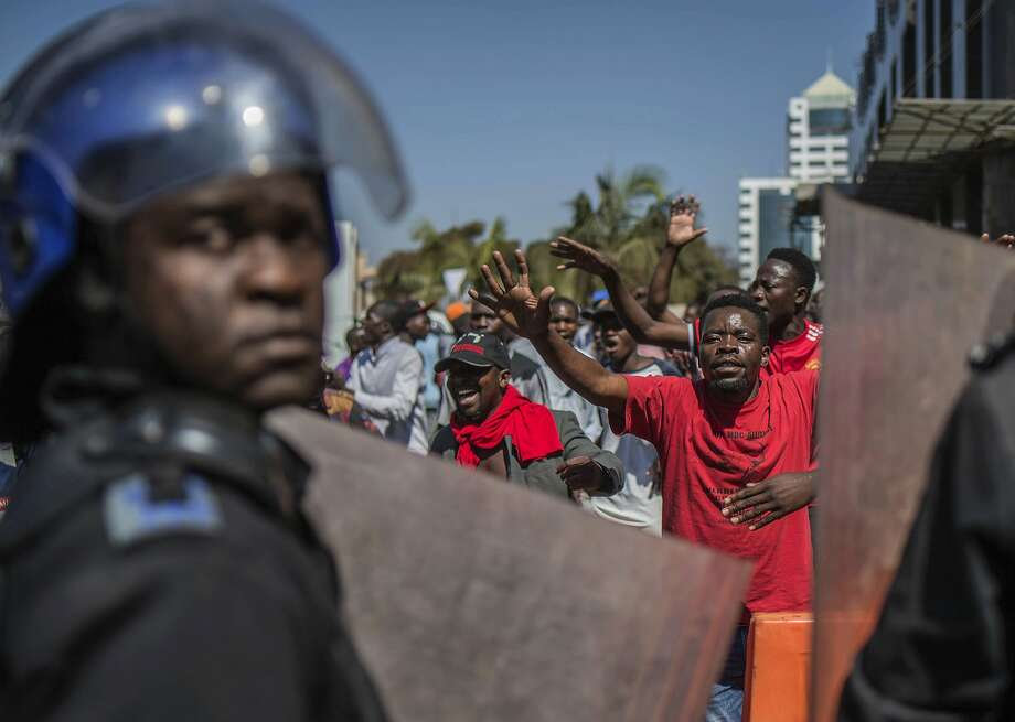 Police patrol outside the Zimbabwe Electoral Commission offices as opposition supporters gather, in the capital, Harare. At least three protesters were reported killed. Photo: Mujahid Safodien / Associated Press