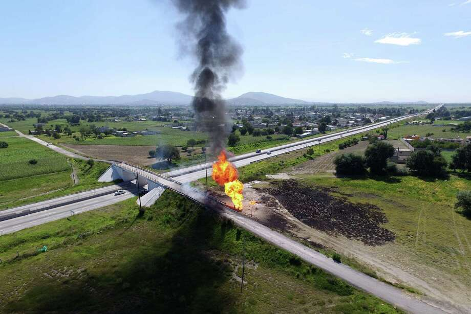 Aerial view taken by a drone showing a fire at a clandestine fuel valve in San Jeronimo Ocotitlan, Acajete, Puebla state, Mexico on July 18, 2018.  Mexico's state-owned petroleum company Pemex has reported a loss of 1,571 million dollars per year due to the theft and traffick of fuel. Puebla state is one of the regions with higher rates of that crime in the country.  / AFP PHOTO / JOSE CASTAÑARESJOSE CASTANARES/AFP/Getty Images Photo: JOSE CASTANARES, AFP/Getty Images / AFP or licensors