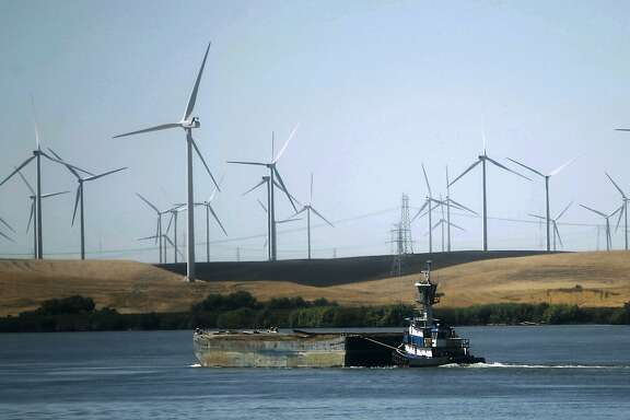 FILE - In this Sept. 23, 2013, file photo, a tugboat pushes a barge down the Sacramento River past wind turbines near Rio Vista, Calif. A contentious proposal to link oversight of California's electric grid with other western states faces a crucial test Tuesday, June 19, 2018, in a state Senate committee. (AP Photo/Rich Pedroncelli, File)