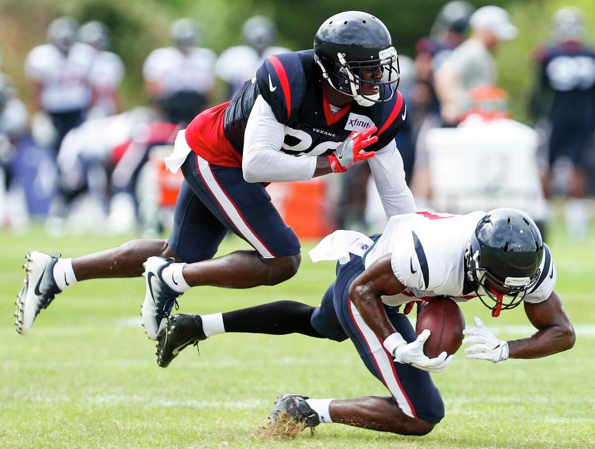 Houston Texans wide receiver Vyncint Smith comes down with a reception against defensive back Johnson Bademosi (20) during training camp at the Greenbrier Sports Performance Center on Wednesday, Aug. 1, 2018, in White Sulphur Springs, W.Va.