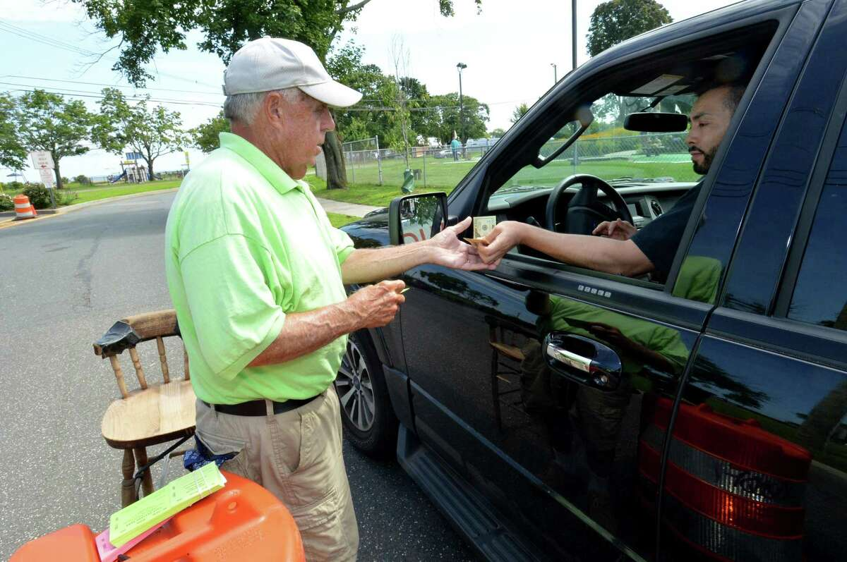 Gate attendant Dick Zakhar collects the $30 weekday fee for non-residents at Calf Pasture Beach on Tuesday in Norwalk.