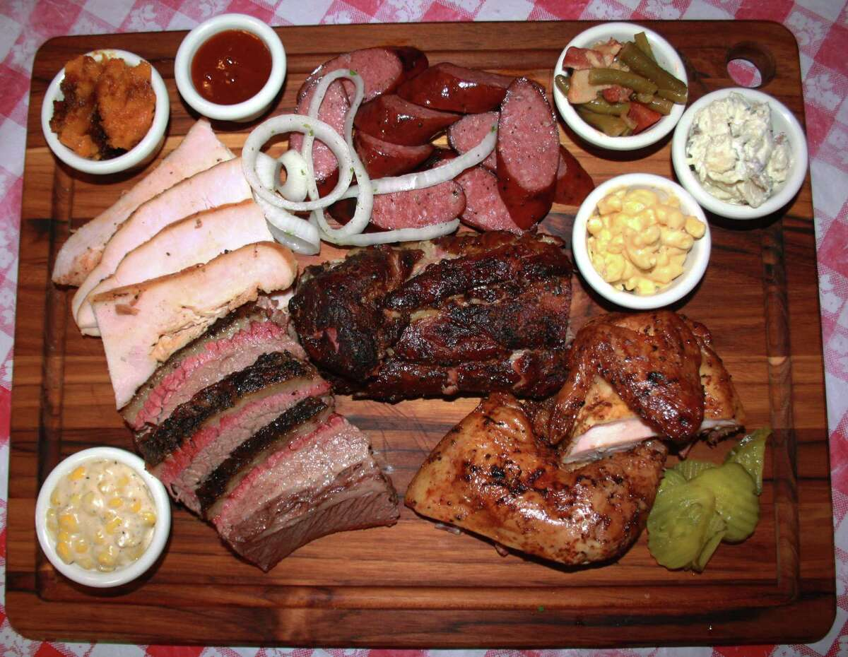 The Dee Willie's BBQ Smokehouse board includes (clockwise from top left): sweet potato casserole, sausage, green beans, baked potato salad, mac-n-cheese, smoked chicken, babyback pork ribs, brisket, creamed corn and turkey.