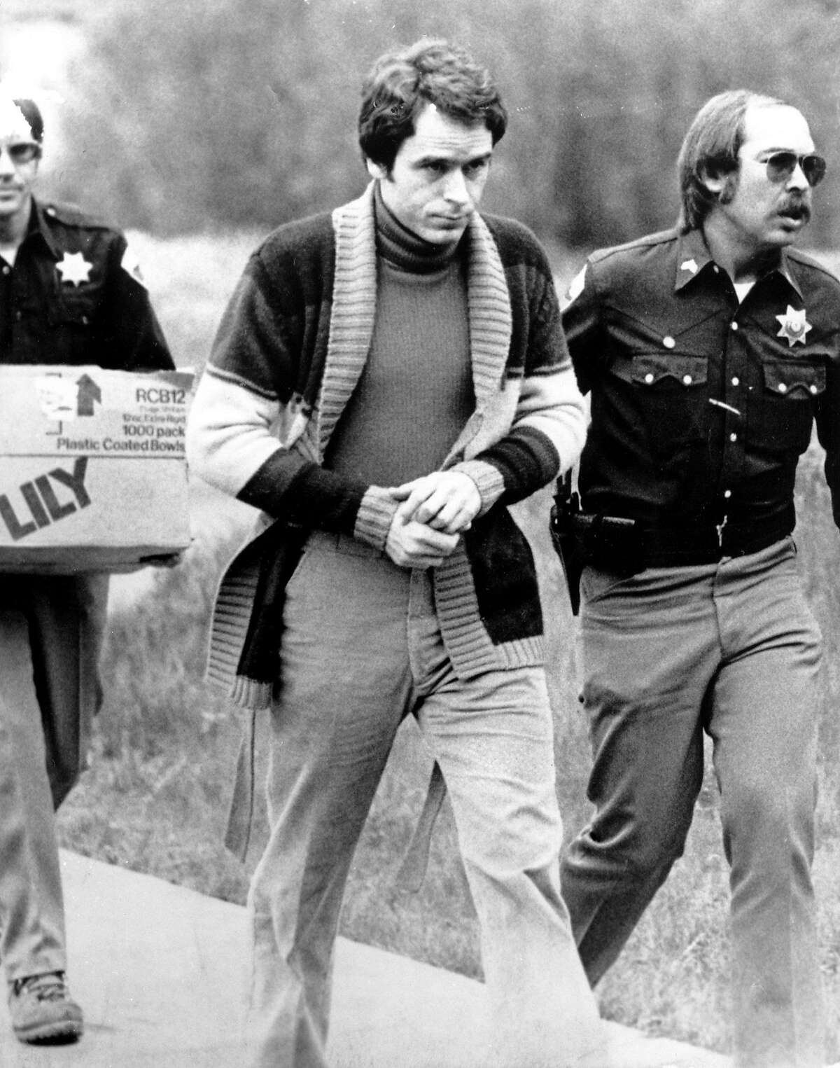Convicted kidnapper Theodore Bundy is led into the Pitkin County courthouse by Deputy Peter Murphy, left, and Rick Kralicek for a hearing in Aspen, Colo., on June 8, 1977. Bundy, who was being charged for murder, jumped out of a second-story window during a court recess. (AP Photo/Mark Levy)