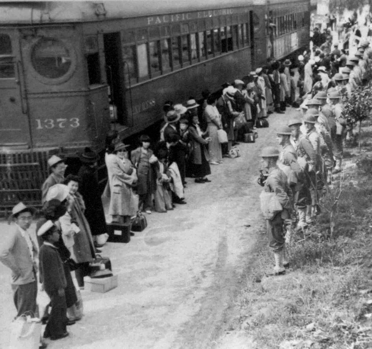 ADVANCE FOR SUNDAY, SEPT. 30--People of Japanese descent line up for a train that will take them from the Santa Anita assembly camp in California to an internment camp at Gila River, Ariz. in 1942. U.S. soldiers face them, right. The internment of Japanese during World War II required the suspension of civil rights for the minority group. (AP Photo/National Archives)