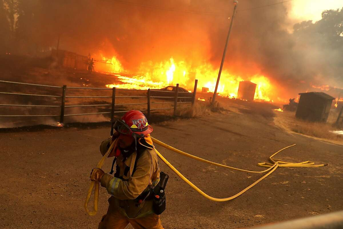 A West Covina firefighter pulls hose away from a barn as the River Fire goes through Lake County.