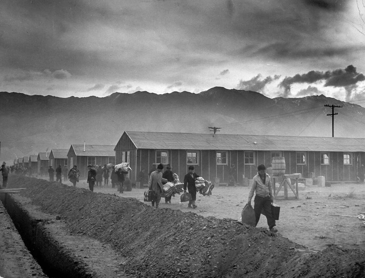 The first group of 82 Japanese-Americans arrive at the Manzanar internment camp (or 'War Relocation Center') carrying their belongings in suitcases and bags, Owens Valley, California, March 21, 1942. Manzanar was one of the first ten internment camps opened in the United States, and it's peak population, before it was closed in Novemeber 1945, was over 10,000 people. (Photo by Eliot Elisofon/The LIFE Picture Collection/Getty Images)