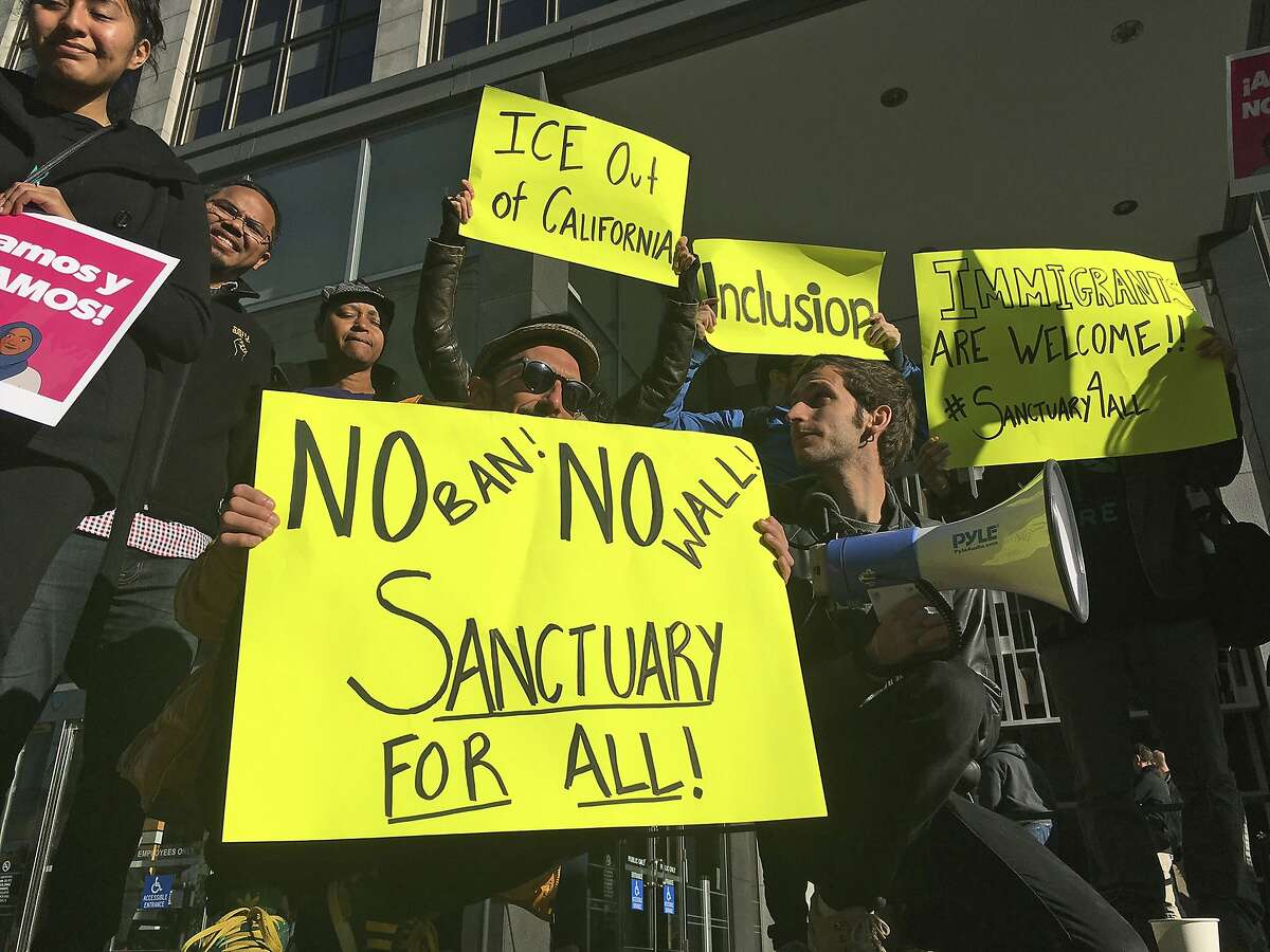 FILE - In this April 14, 2017, file photo, protesters hold up signs outside a courthouse in San Francisco. President Donald Trump's executive order threatening to withhold funding from