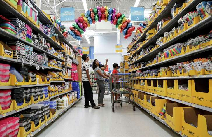 Kavita Charmarti, center, shops for back-to-school supplies with her son Saket, 14, left, and Akhil, 10, right, at a Walmart store, Tuesday, July 24, 2018, in Sugar Land.