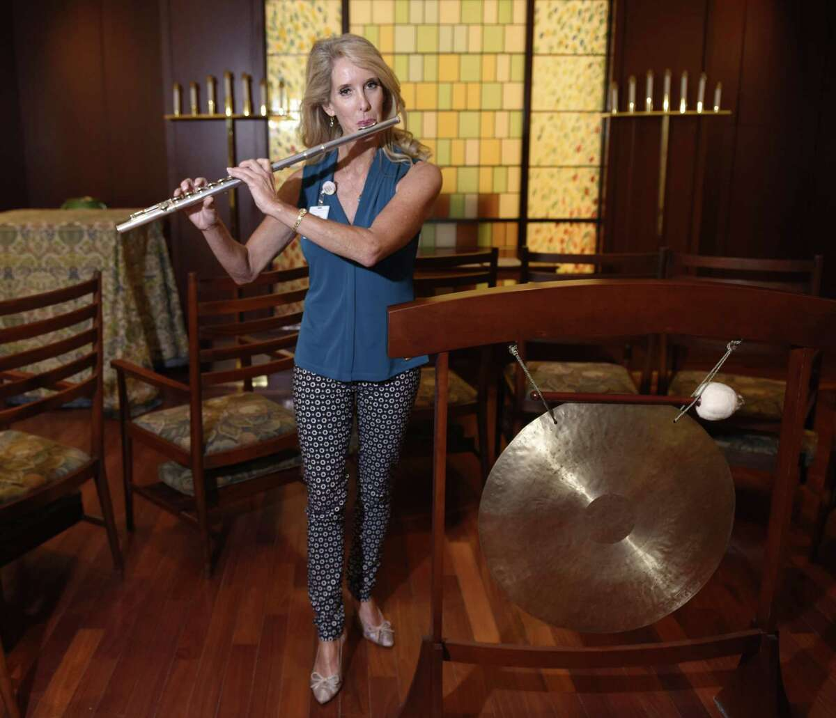 Music therapist Dr. Amy Zabin plays the flute beside her gong, two aspects of her music therapy, at Greenwich Hospital in Greenwich on Wednesday.