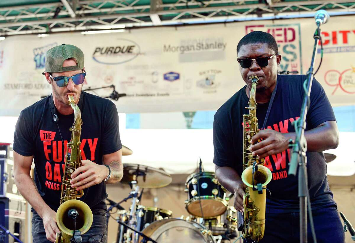 From left, Tommy Weeks of Ridgefield and Colin Walters of Stamford along with members of the Funky Dawgz Brass Band open up for Trombone Shorty and Orleans Avenue as they perform the final Wednesday Night Live concert at Columbus Park in Stamford, Connecticut on August 1, 2018.